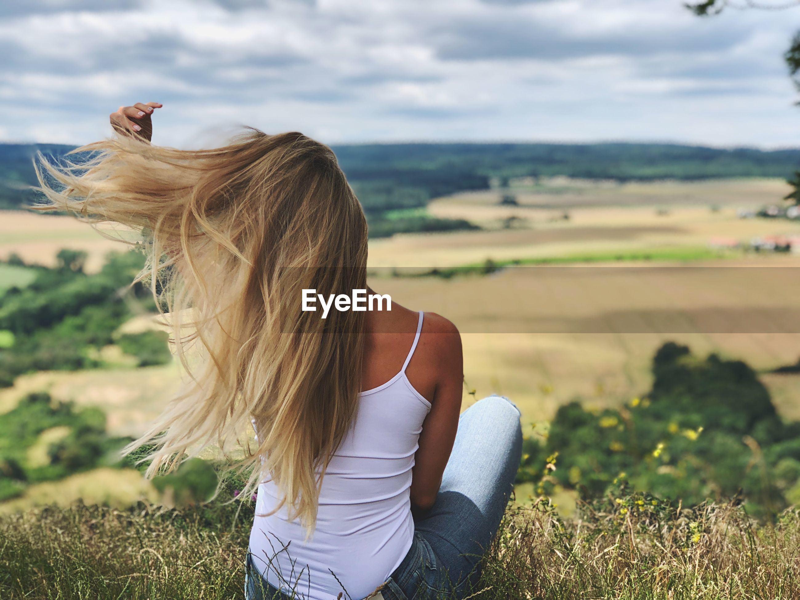 Rear view of woman with long hair looking at landscape while sitting on field