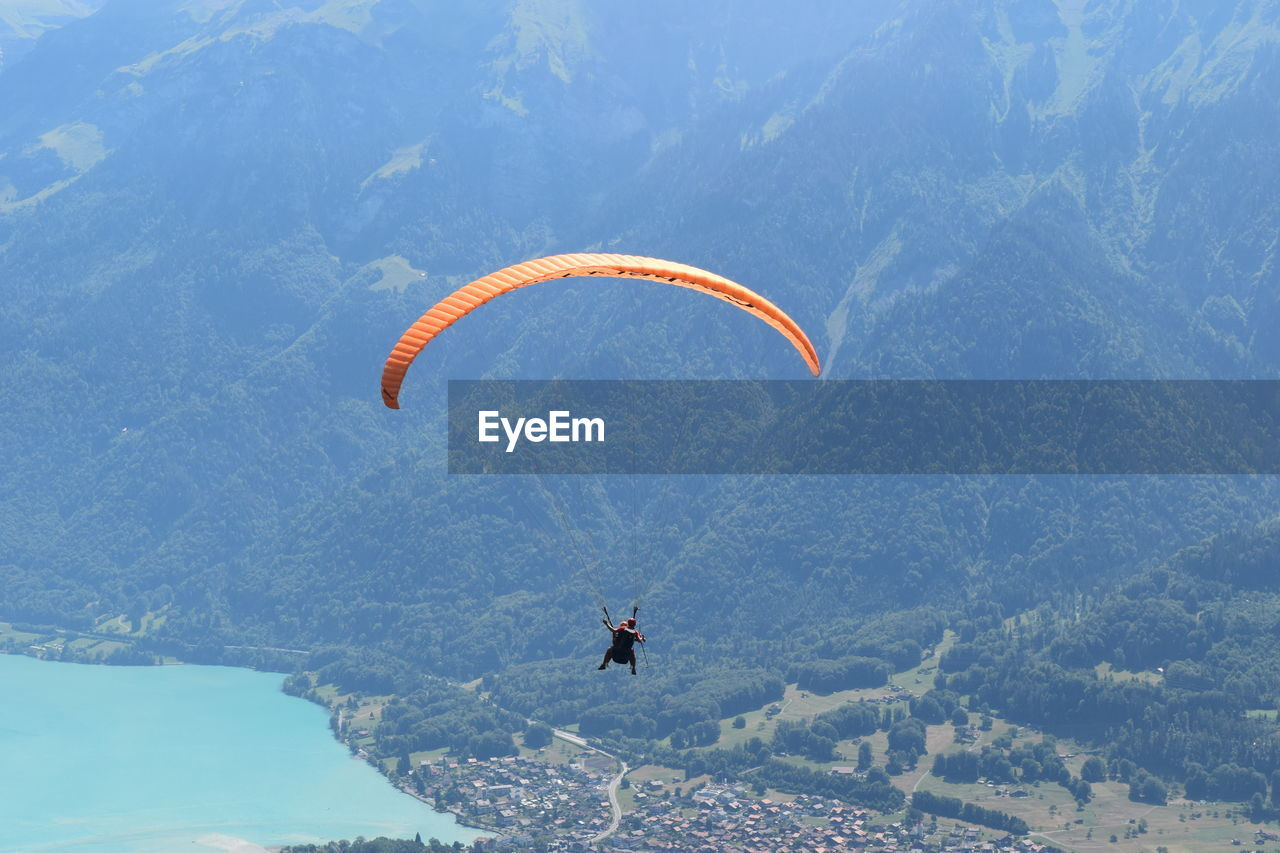 mid-air, parachute, flying, extreme sports, adventure, paragliding, exhilaration, one person, gliding, leisure activity, day, real people, nature, mountain, skydiving, outdoors, sport, low angle view, scenics, beauty in nature, tree, sky, people