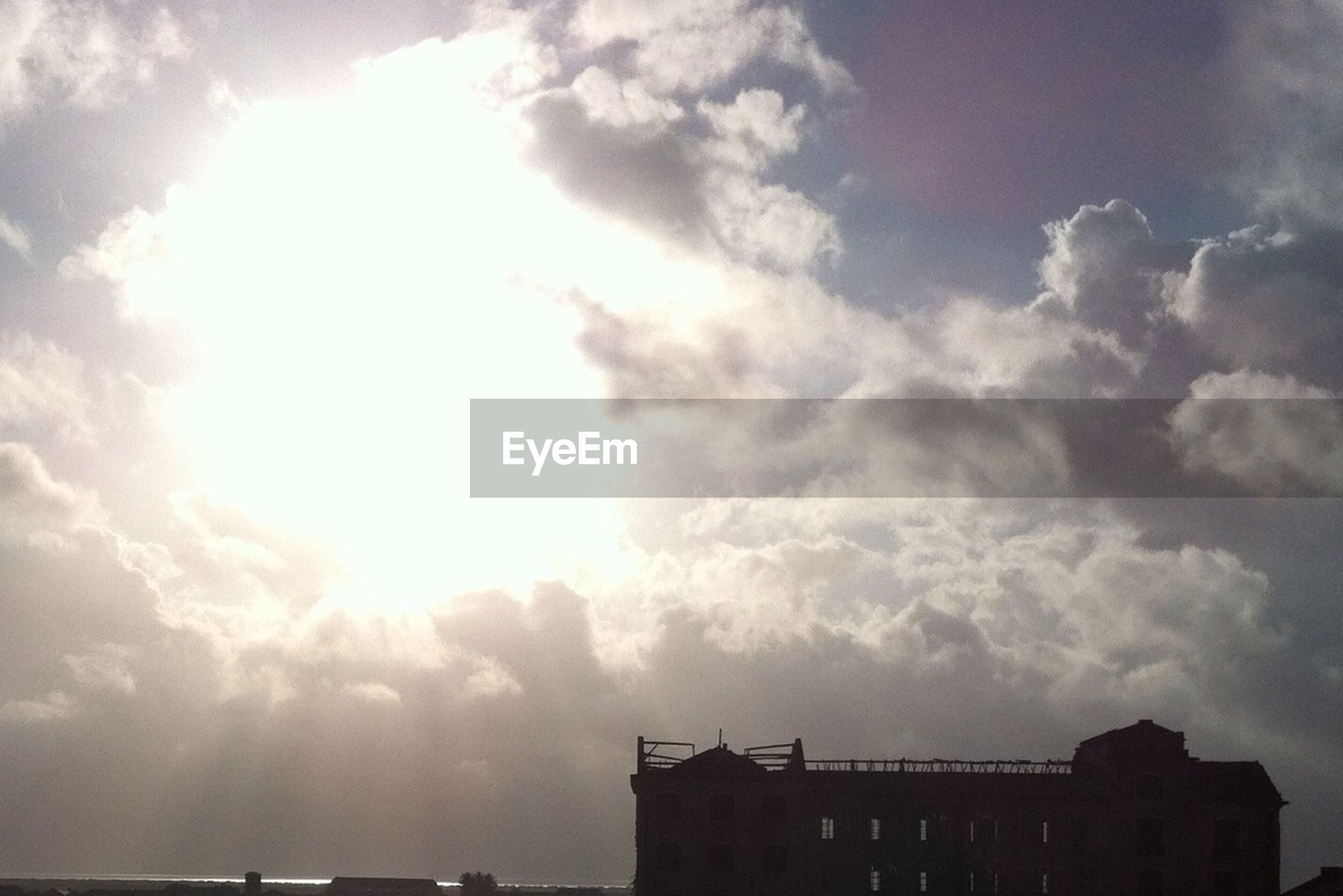 sky, building exterior, architecture, built structure, sun, cloud - sky, low angle view, sunbeam, sunlight, cloud, cloudy, silhouette, lens flare, nature, outdoors, building, beauty in nature, no people, sunset, day