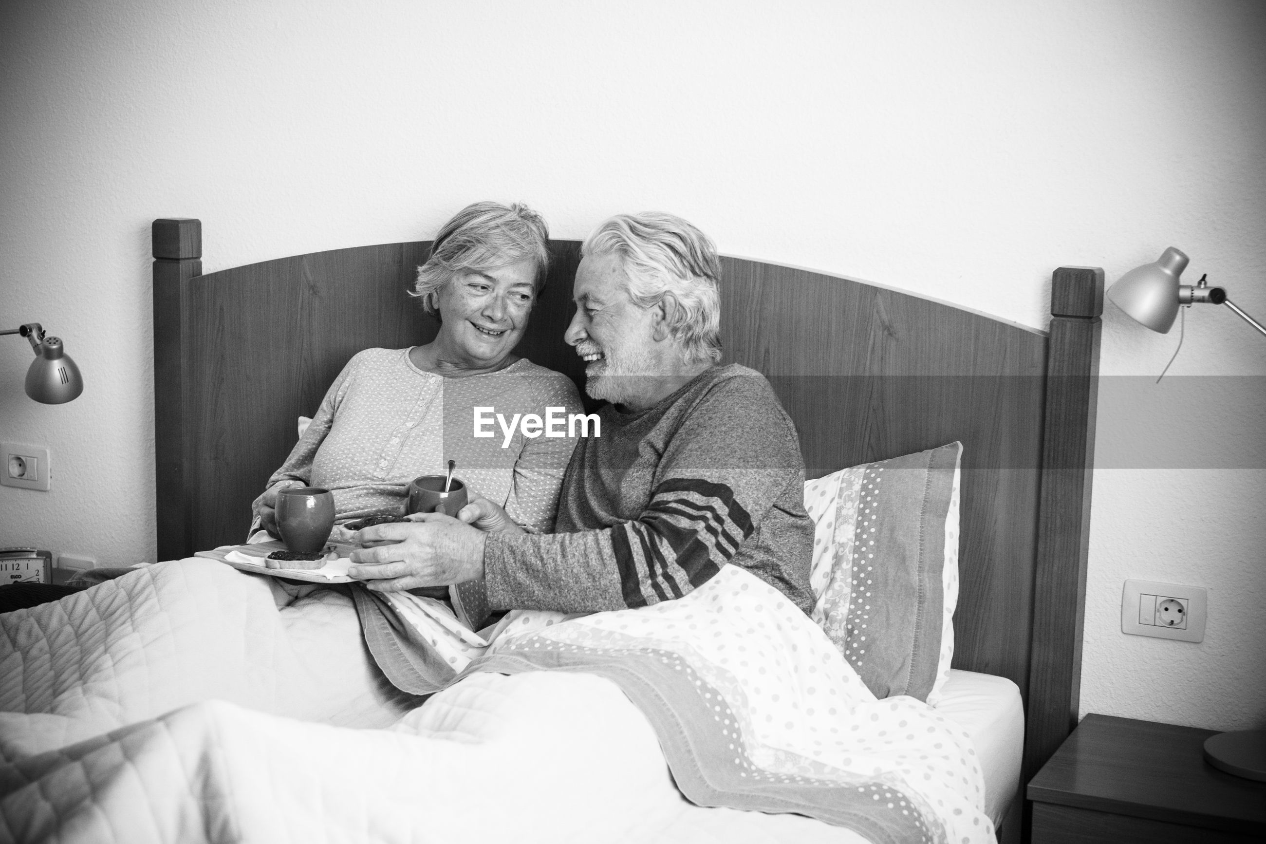 Senior couple relaxing on bed at home