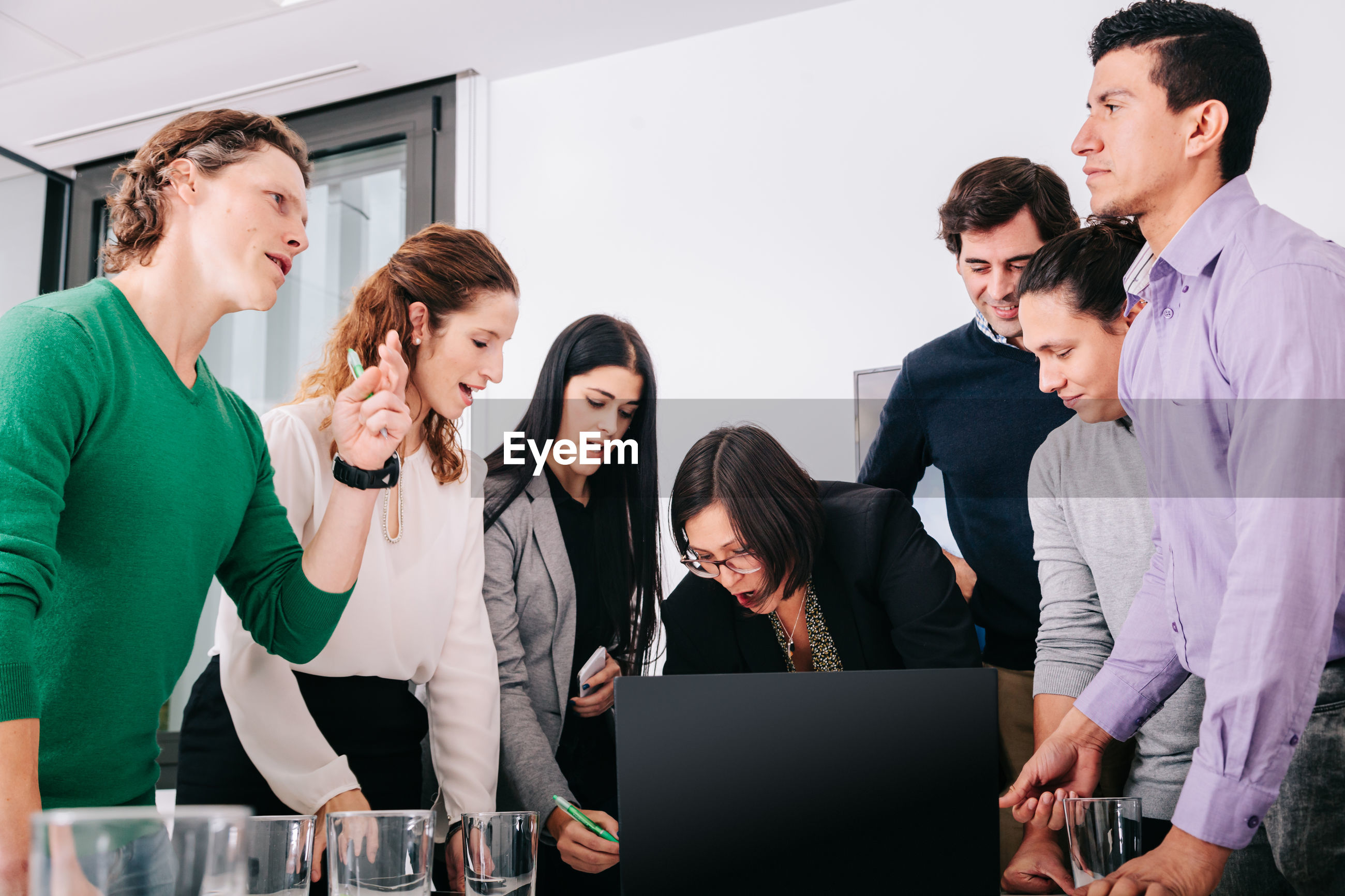 Business people discussing over laptop in office