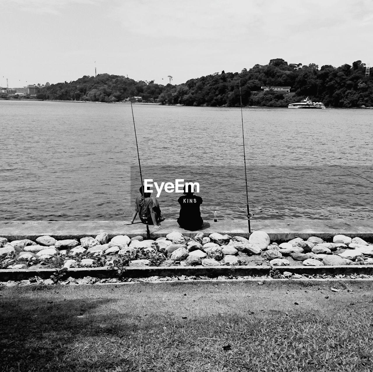 Rear View Of Men Fishing In Sea