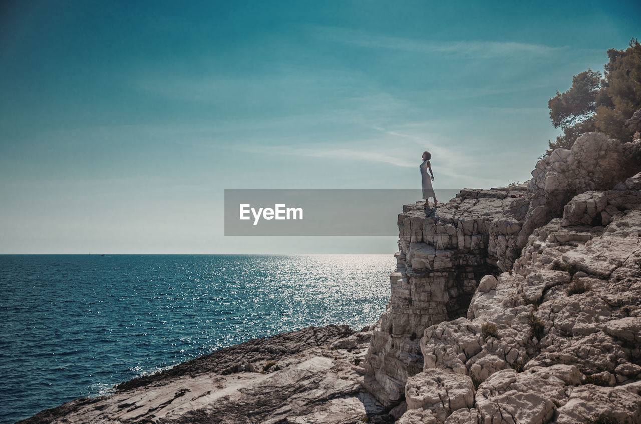 Teenage girl standing on cliff by sea against sky
