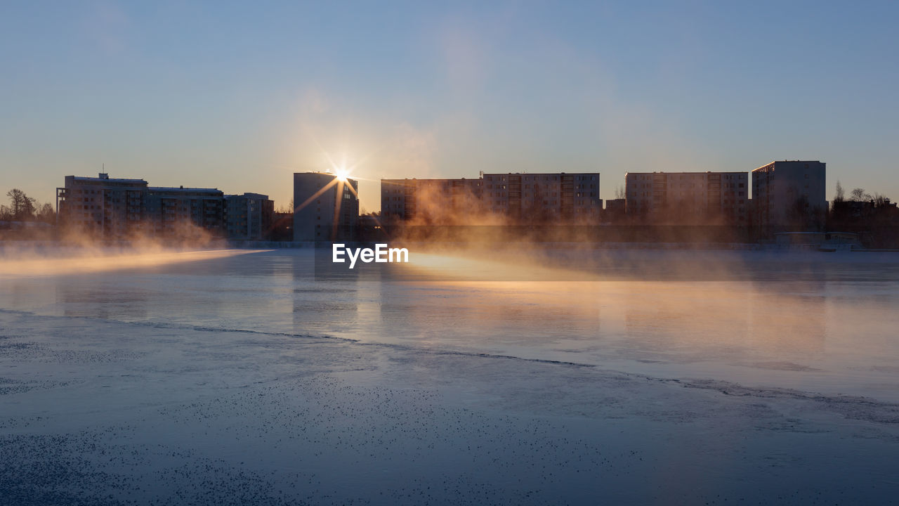 sky, building exterior, architecture, nature, built structure, sunset, city, no people, water, sunlight, smoke - physical structure, sun, clear sky, steam, outdoors, building, sunbeam, winter, lens flare