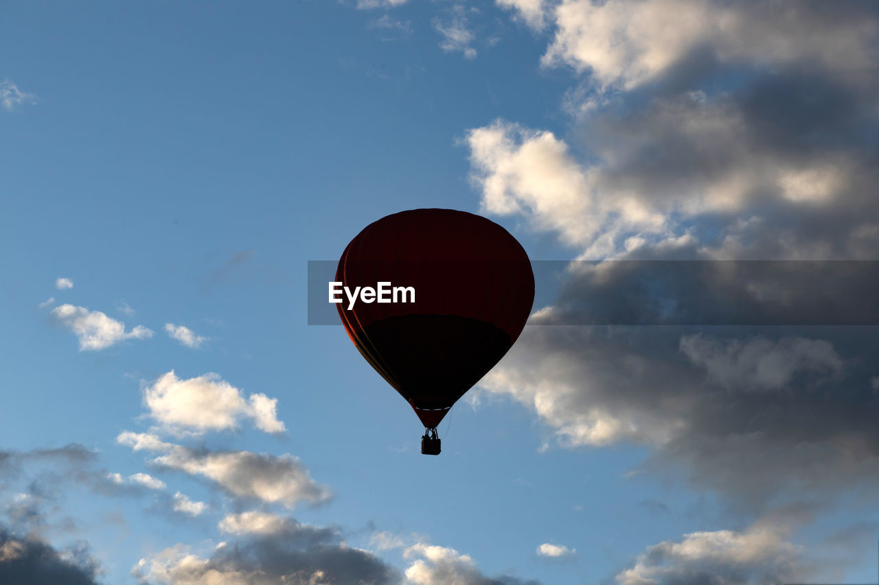 sky, cloud - sky, mid-air, low angle view, flying, balloon, adventure, transportation, air vehicle, nature, freedom, hot air balloon, parachute, red, day, extreme sports, beauty in nature, no people, outdoors, sport