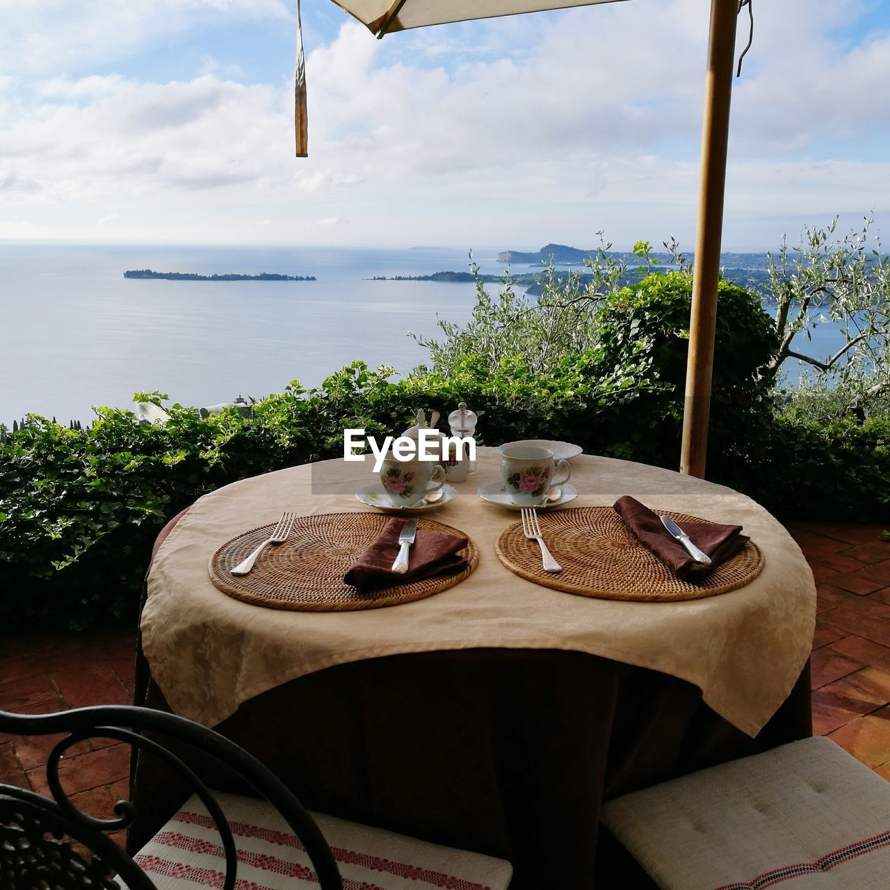 table, sky, food and drink, cloud - sky, day, sea, no people, chair, nature, water, food, place setting, outdoors, tree, scenics, plate, drink, luxury, beauty in nature, horizon over water, freshness, close-up