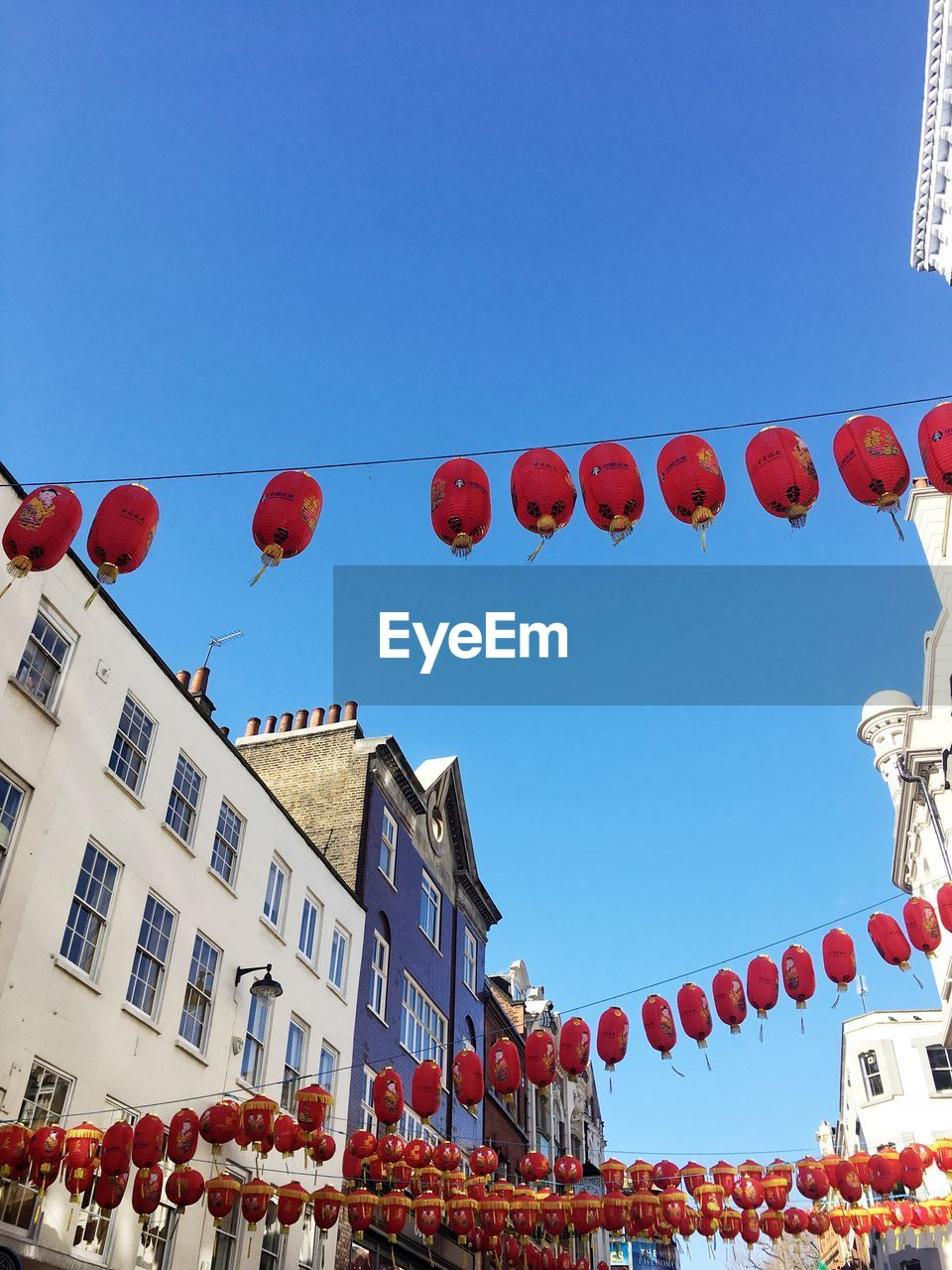 hanging, low angle view, celebration, chinese lantern, decoration, lantern, traditional festival, cultures, red, chinese lantern festival, chinese new year, in a row, lighting equipment, building exterior, architecture, built structure, text, day, outdoors, tradition, clear sky, blue, no people, city, sky