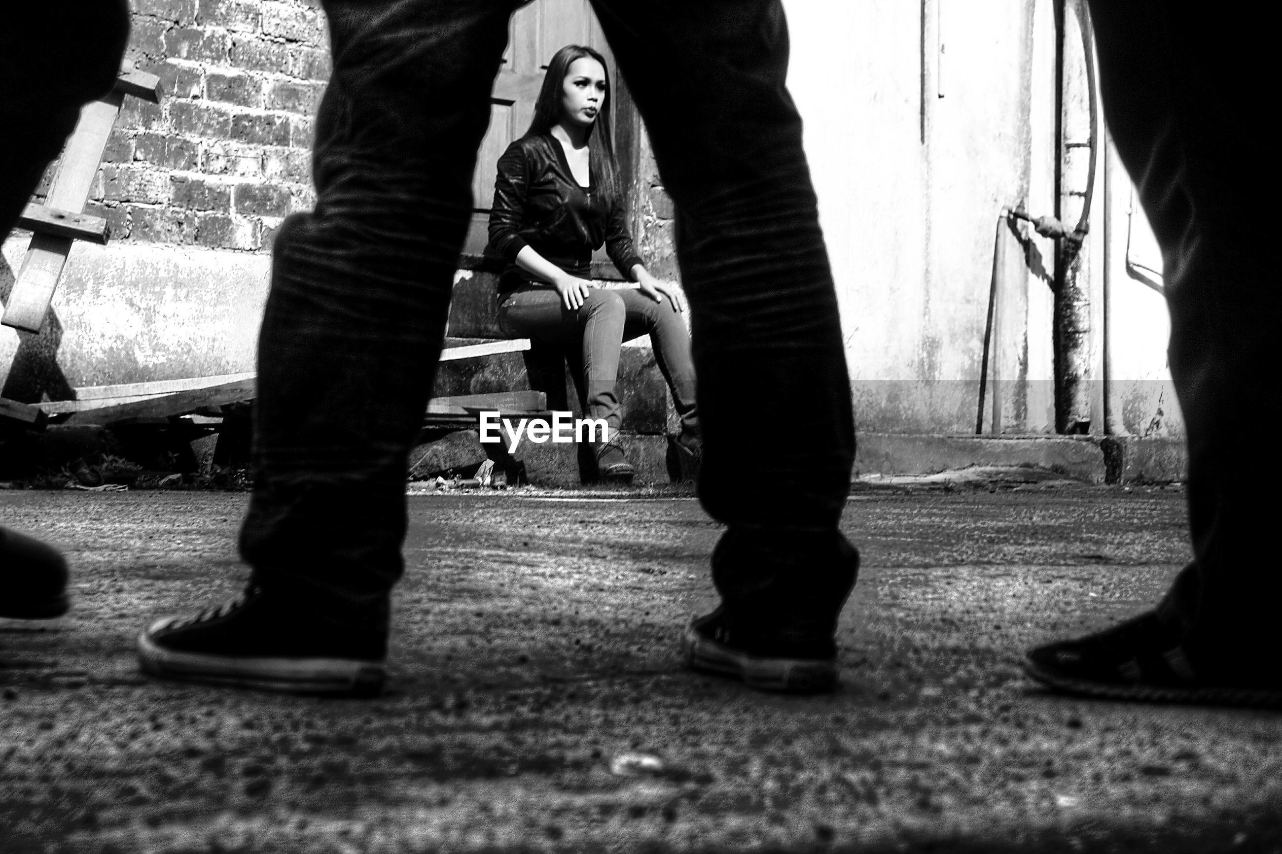 Woman sitting on steps seen through legs