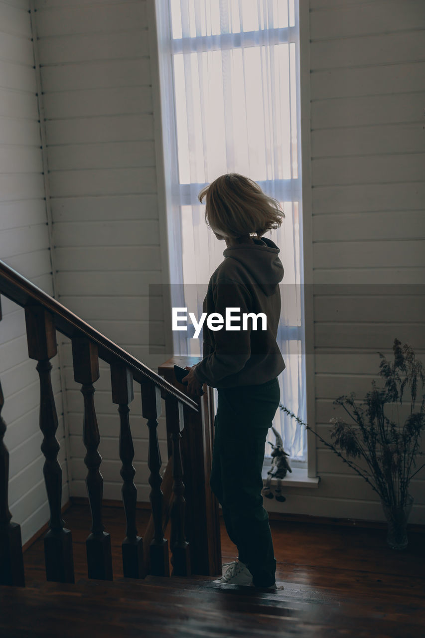 Side view of girl standing by railing at home