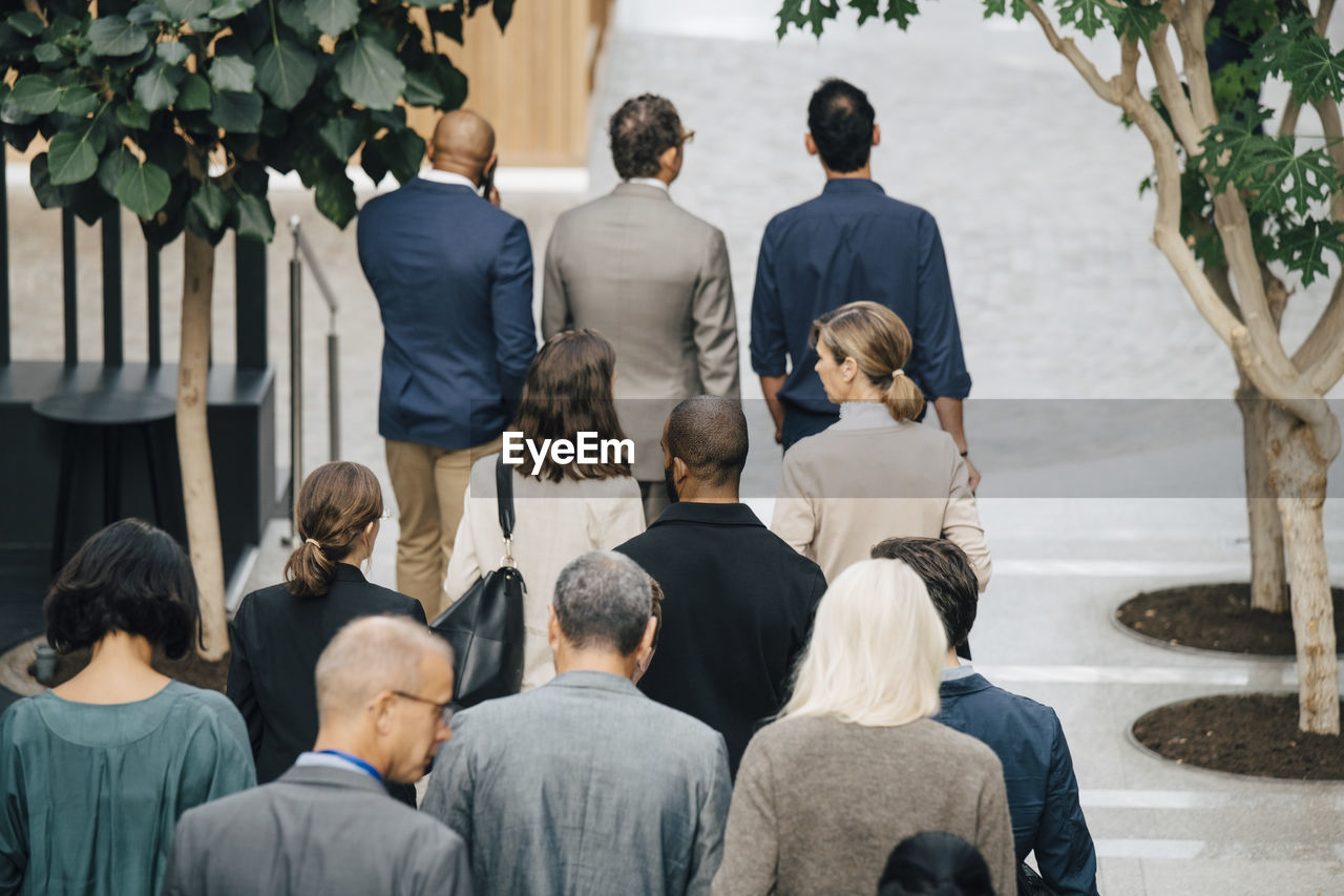 REAR VIEW OF PEOPLE STANDING IN FRONT OF OFFICE