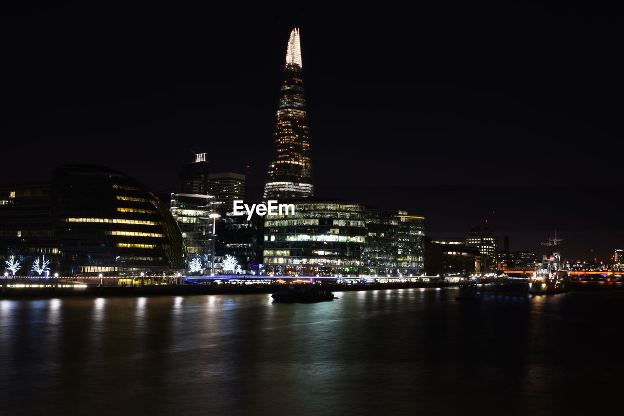 architecture, building exterior, built structure, illuminated, night, city, water, building, travel destinations, sky, tall - high, office building exterior, waterfront, cityscape, reflection, tower, skyscraper, river, no people, modern, outdoors, financial district, spire, passenger craft