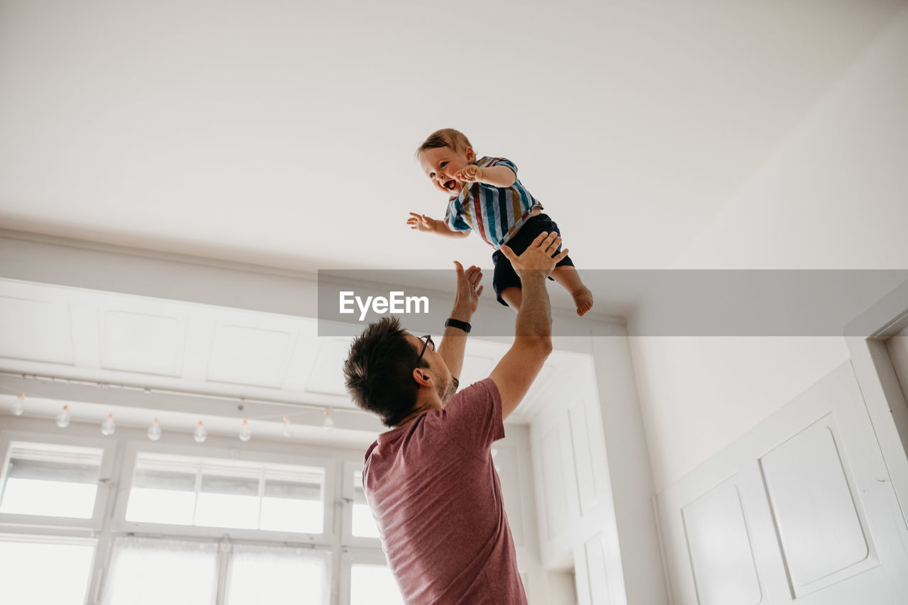 Low Angle View Of Playful Father Catching Son At Home
