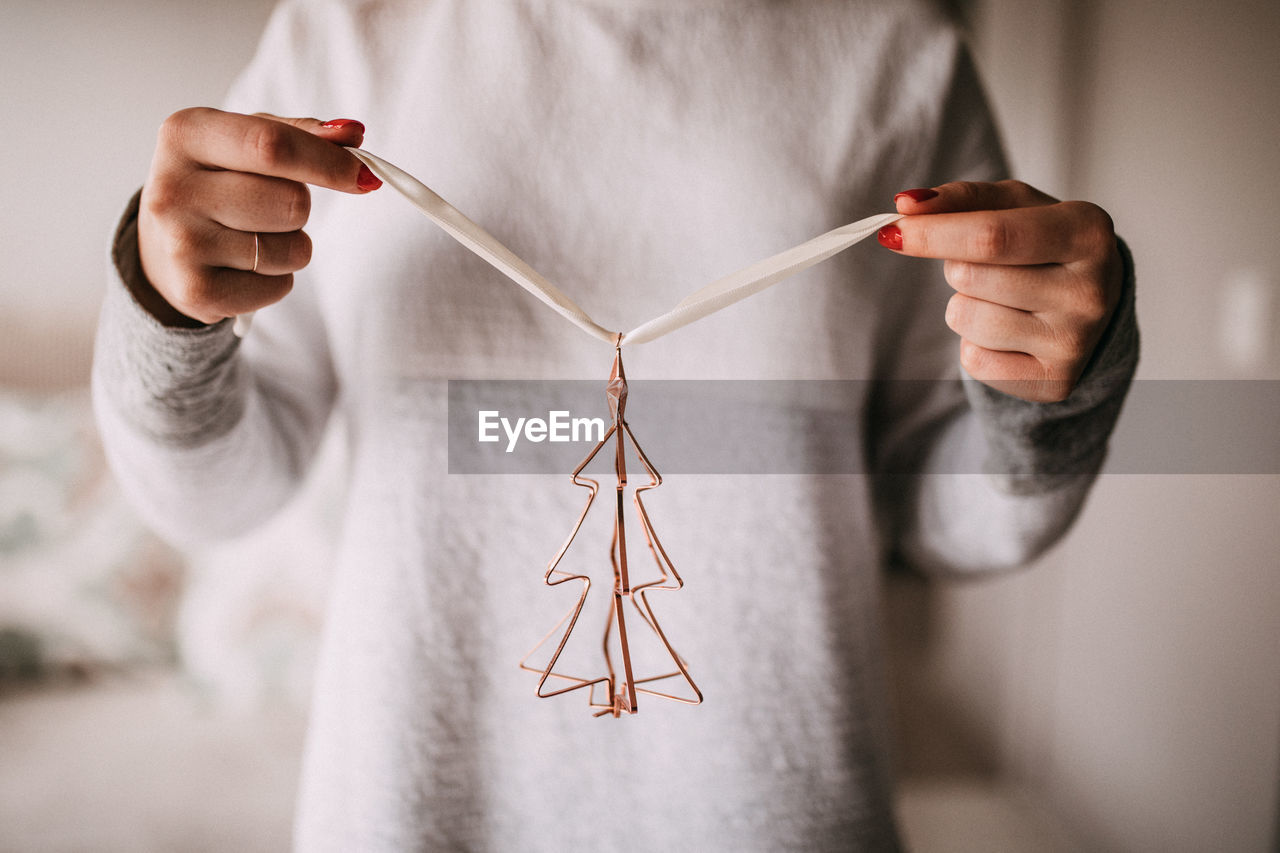 Midsection of woman holding christmas decoration