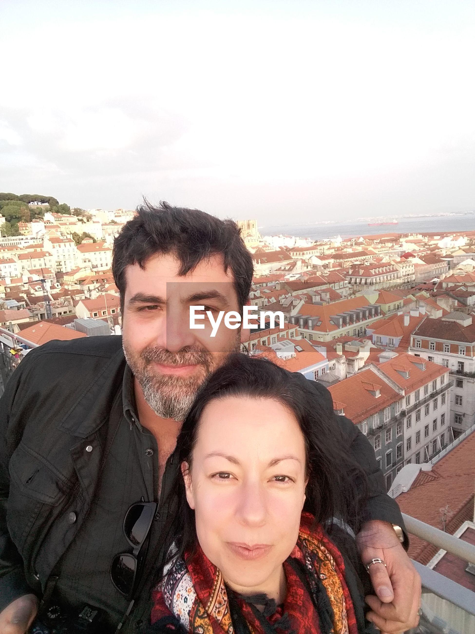 Portrait of smiling mature couple against cityscape