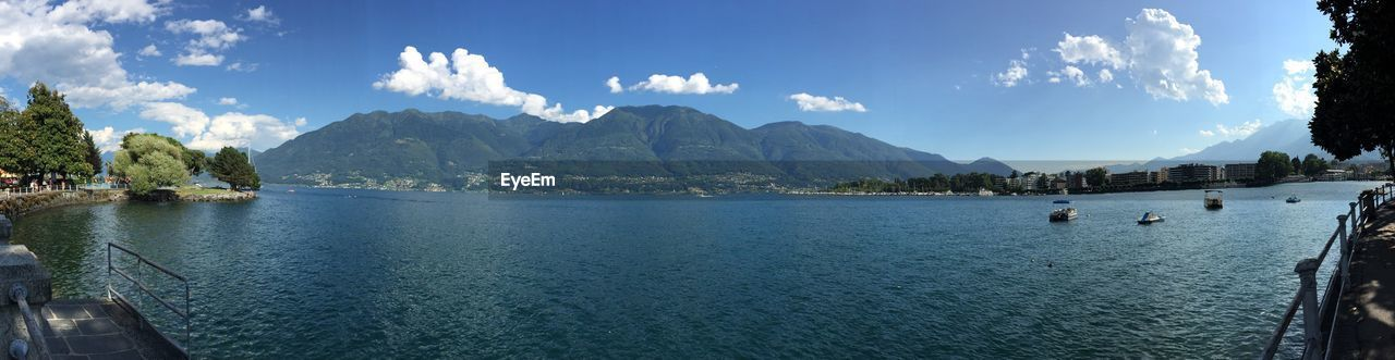 water, mountain, sky, outdoors, scenics, day, travel destinations, nature, tranquil scene, beauty in nature, tourism, tree, nautical vessel, tranquility, panoramic, blue, mountain range, vacations, sea, no people, architecture