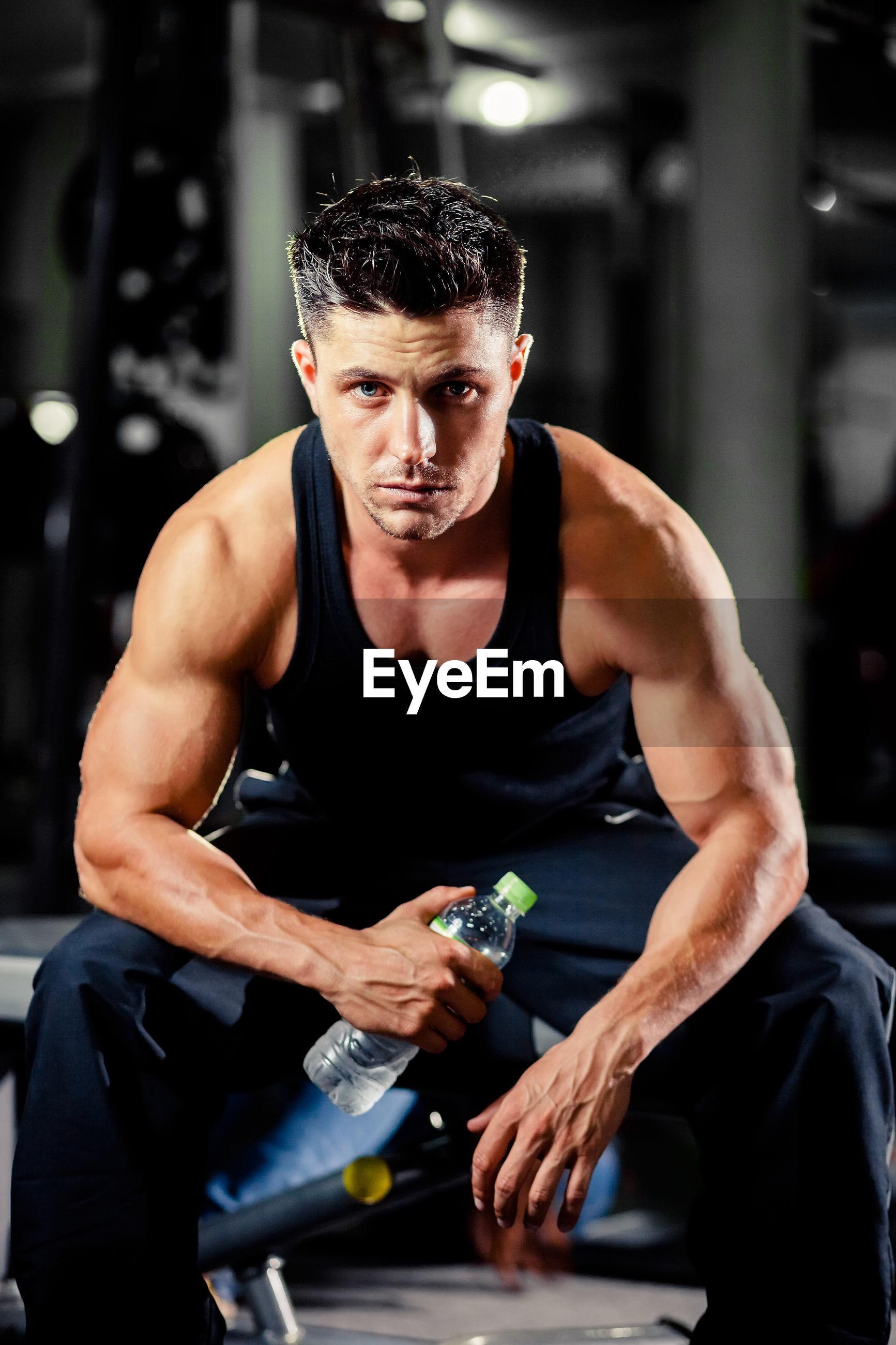 Portrait of muscular man sitting at gym