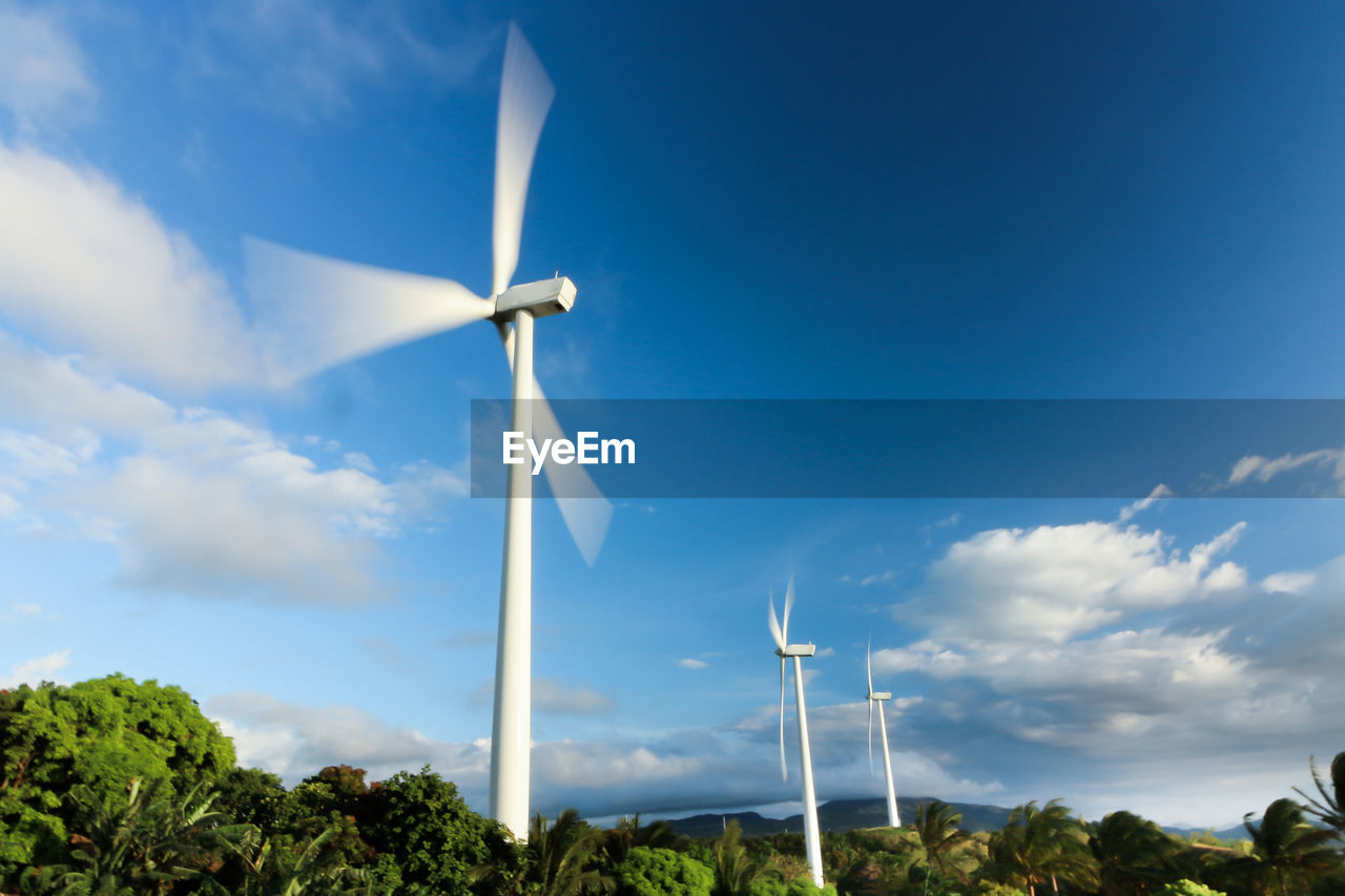Blurred Motion Of Wind Turbines Against Blue Sky