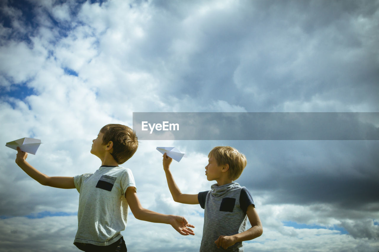Boys playing with paper airplane against cloudy sky