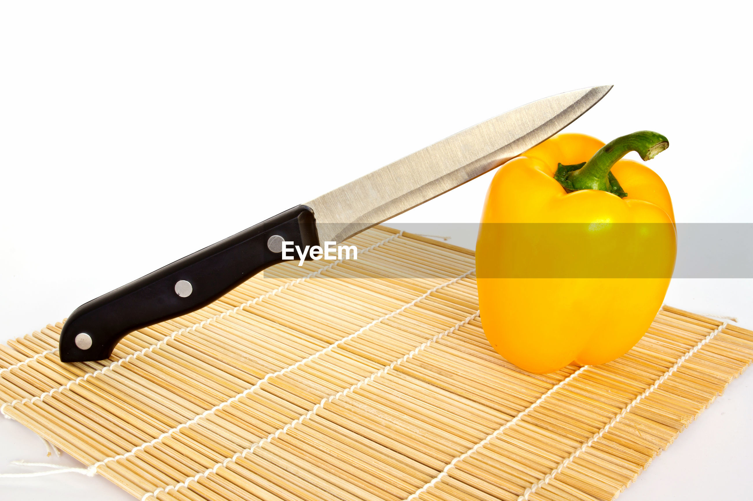 Knife and yellow bell pepper on place mat over white background