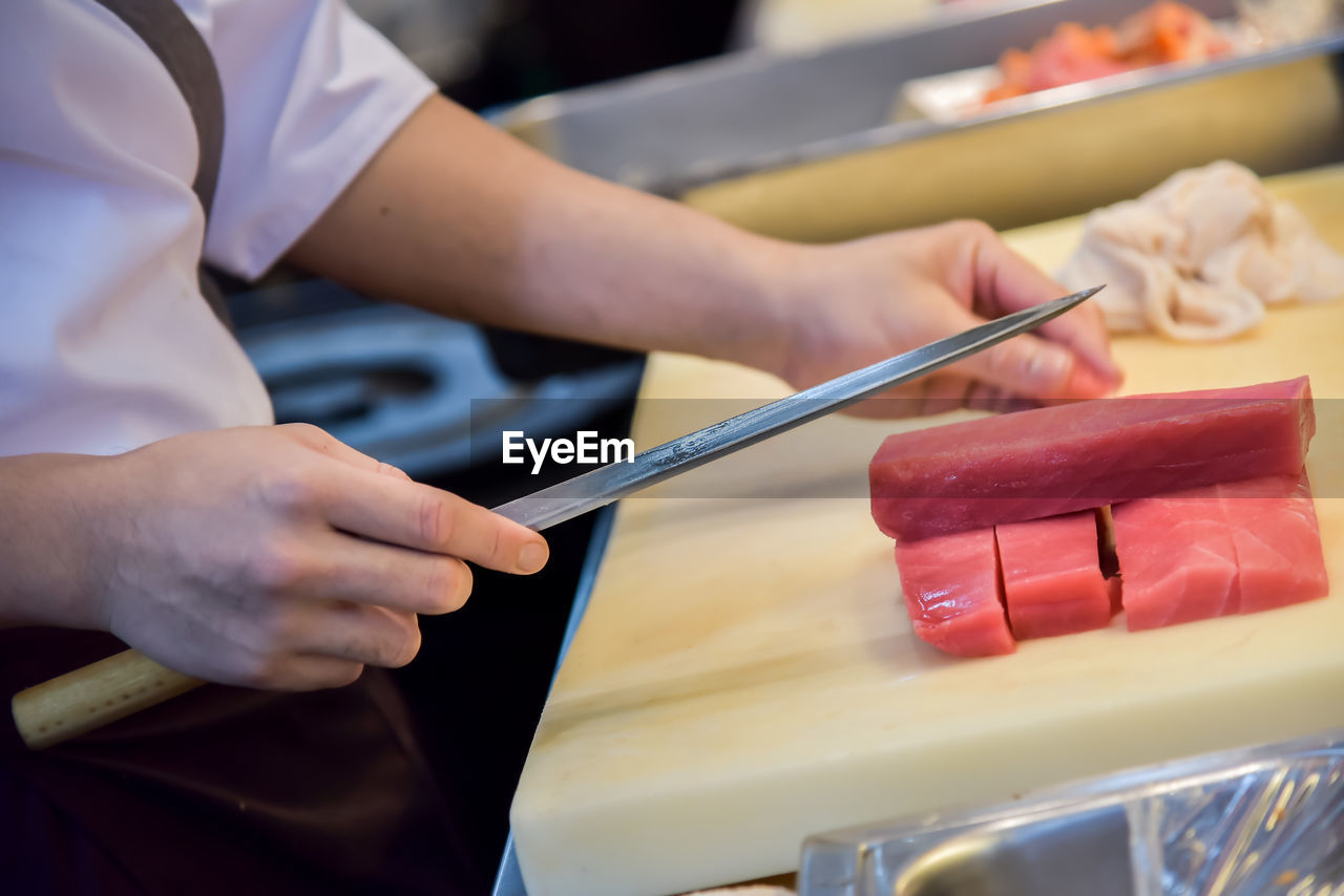 Midsection of chef cutting meat in commercial kitchen