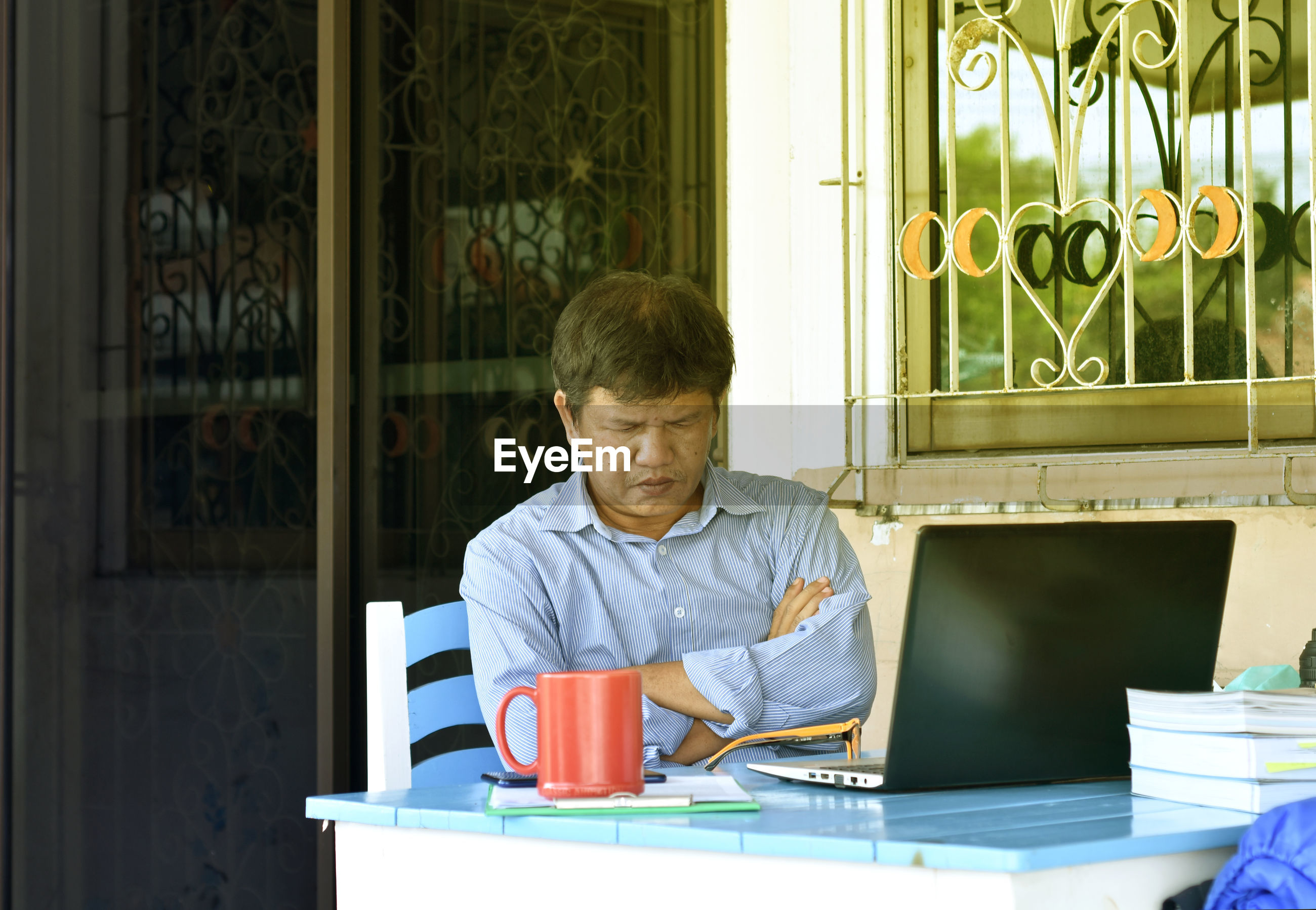 MID ADULT MAN SITTING IN COFFEE CUP
