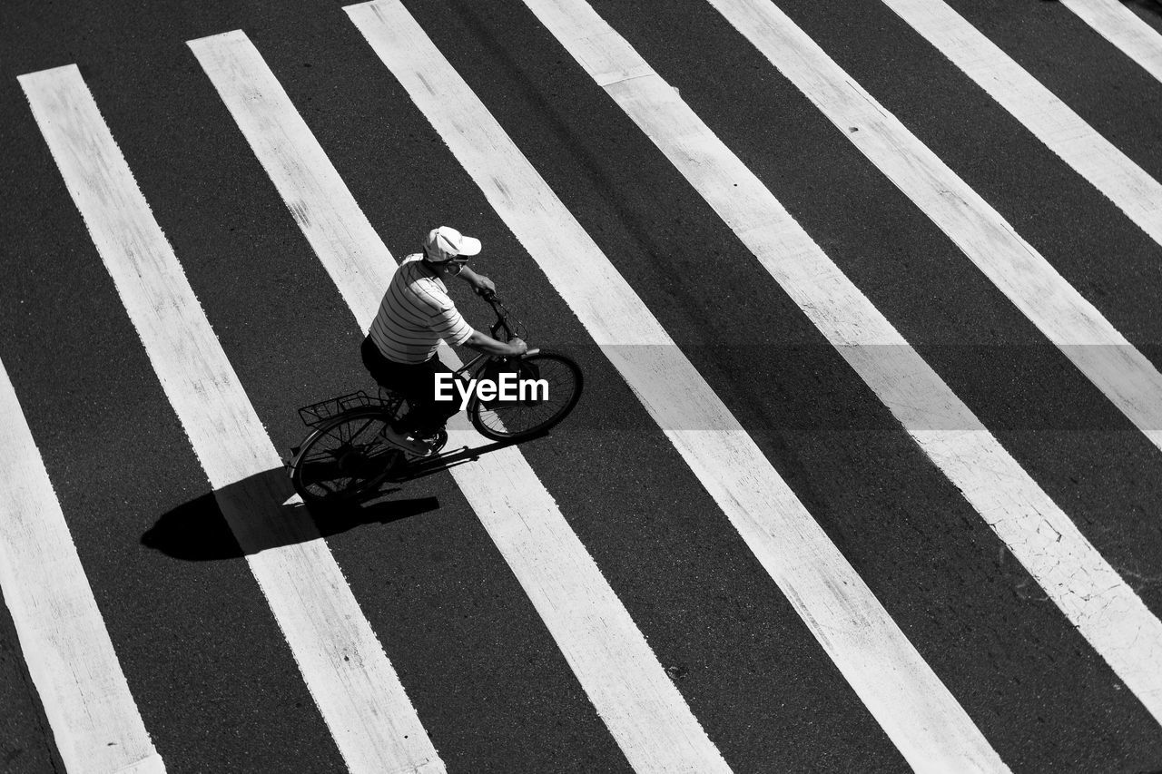 High angle view of man riding bicycle on zebra crossing