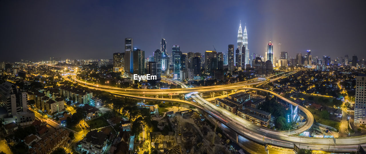 illuminated, architecture, night, city, building exterior, skyscraper, built structure, speed, modern, cityscape, outdoors, travel destinations, downtown district, light trail, transportation, sky, no people, urban skyline