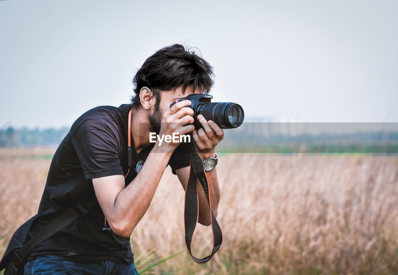 Young man photographing on field