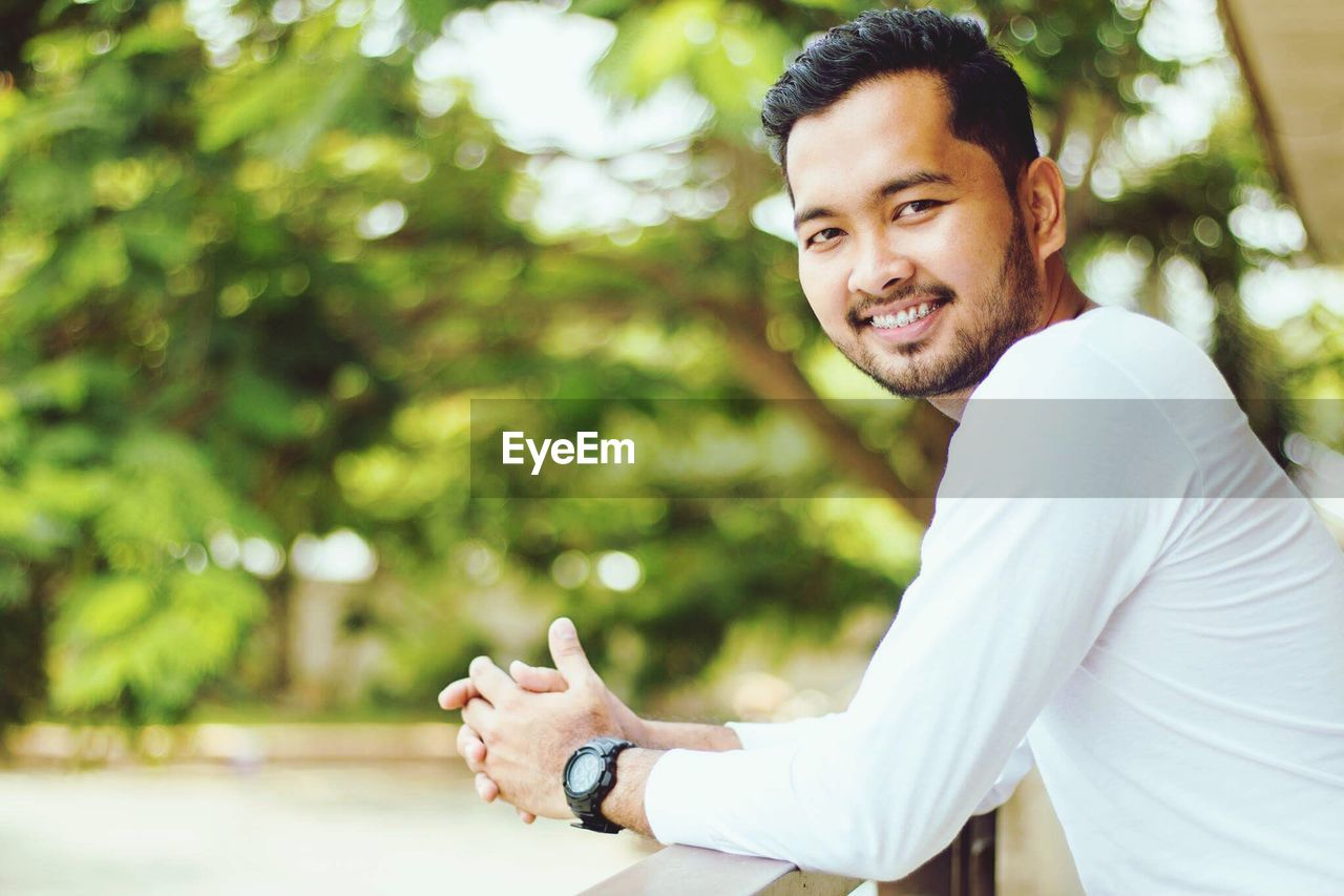 looking at camera, portrait, real people, one person, smiling, focus on foreground, casual clothing, lifestyles, outdoors, day, young men, gesturing, happiness, sitting, young adult, leisure activity, tree, cheerful, men, nature, wireless technology, thumbs up, human hand
