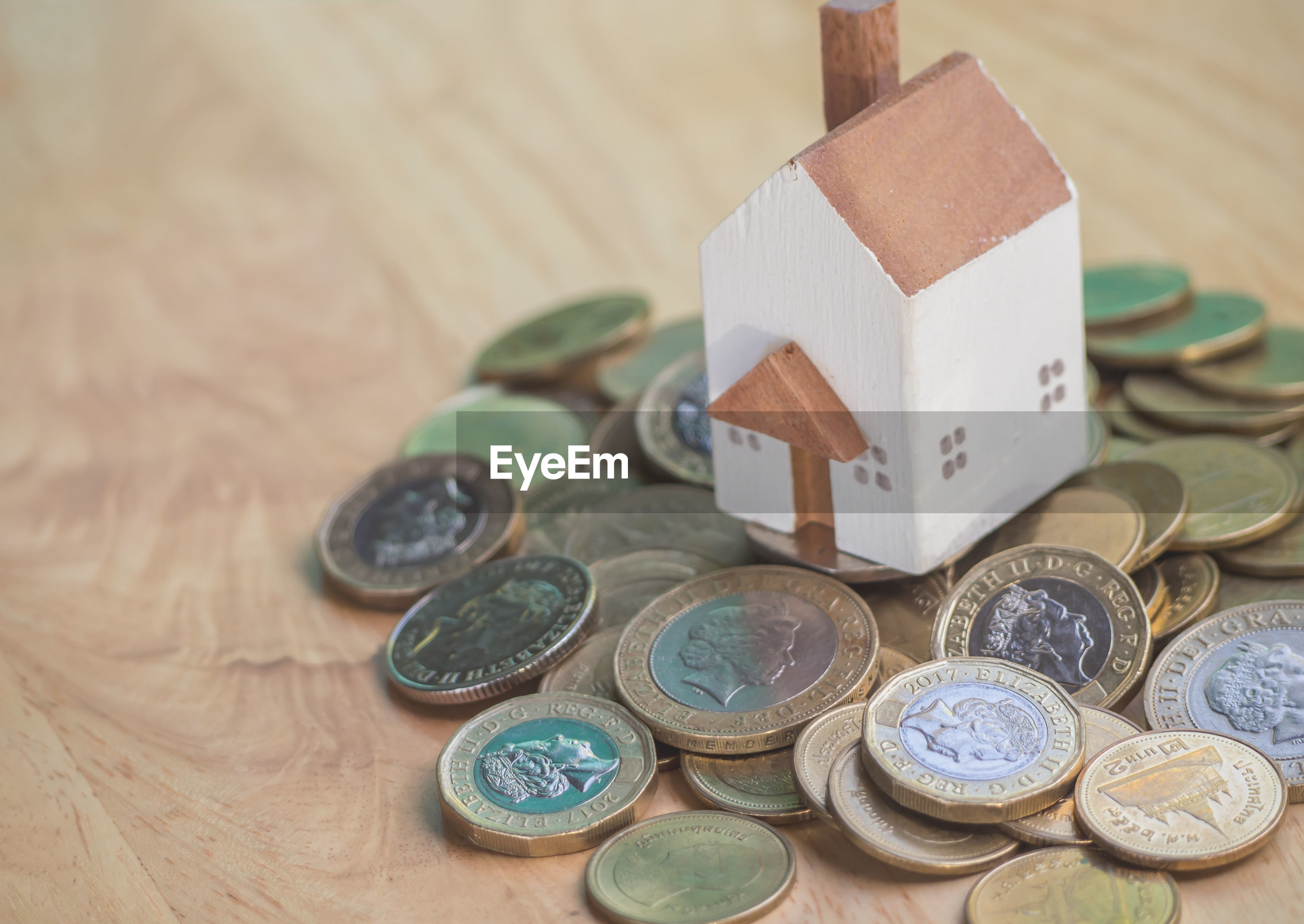 Close-up of coins and toy home on table