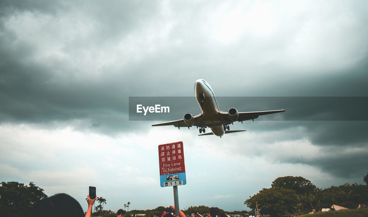 cloud - sky, sky, air vehicle, airplane, mode of transportation, transportation, nature, low angle view, flying, tree, no people, day, sign, plant, overcast, communication, travel, outdoors, on the move, plane