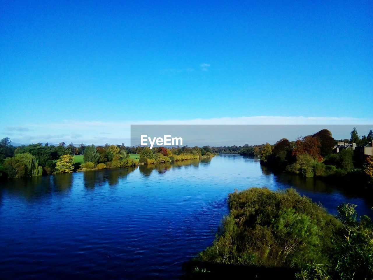 water, tranquil scene, blue, nature, scenics, tranquility, beauty in nature, river, tree, no people, holiday, outdoors, waterfront, clear sky, landscape, forest, day, sky, view into land