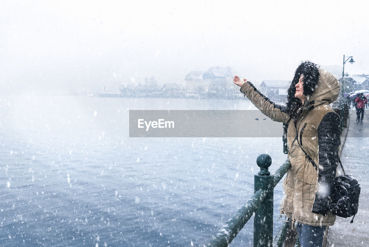 winter, cold temperature, one person, warm clothing, snow, nature, water, standing, adult, day, clothing, snowing, copy space, young adult, women, real people, outdoors, human arm
