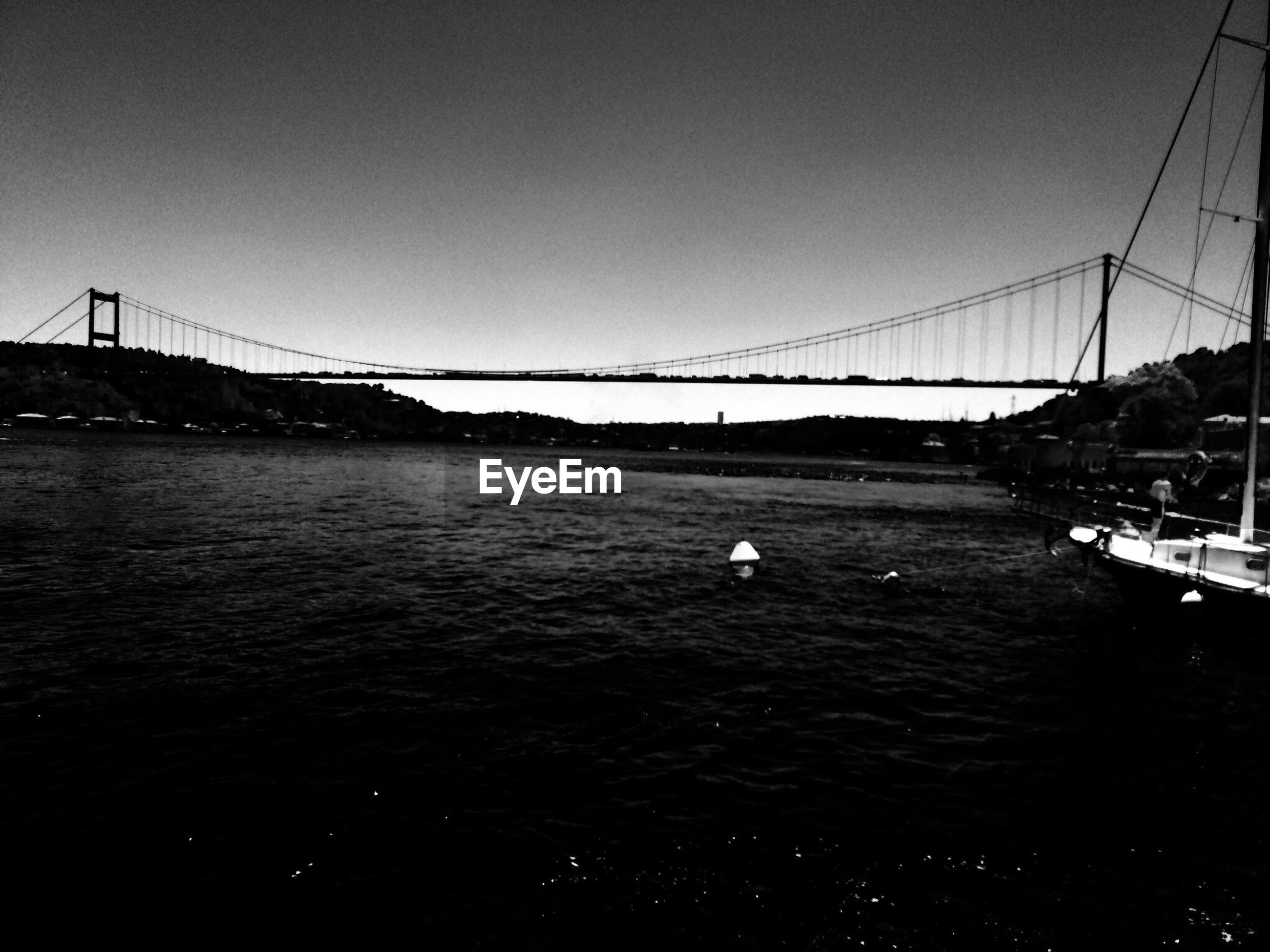 connection, bridge - man made structure, water, clear sky, transportation, animal themes, bird, river, built structure, architecture, copy space, suspension bridge, bridge, nautical vessel, engineering, one animal, animals in the wild, wildlife, waterfront, outdoors