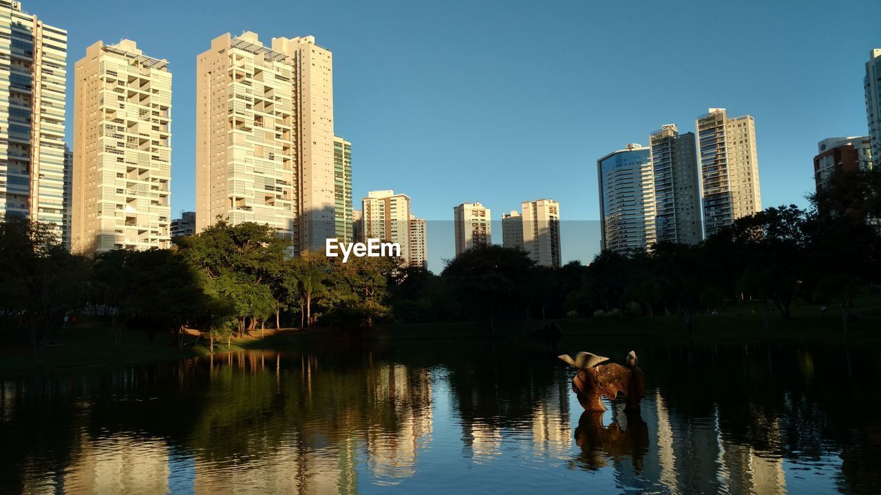 architecture, building exterior, water, built structure, skyscraper, tree, waterfront, reflection, lake, outdoors, clear sky, city, day, no people, sky, urban skyline, growth, nature, animal themes, modern, mammal, cityscape