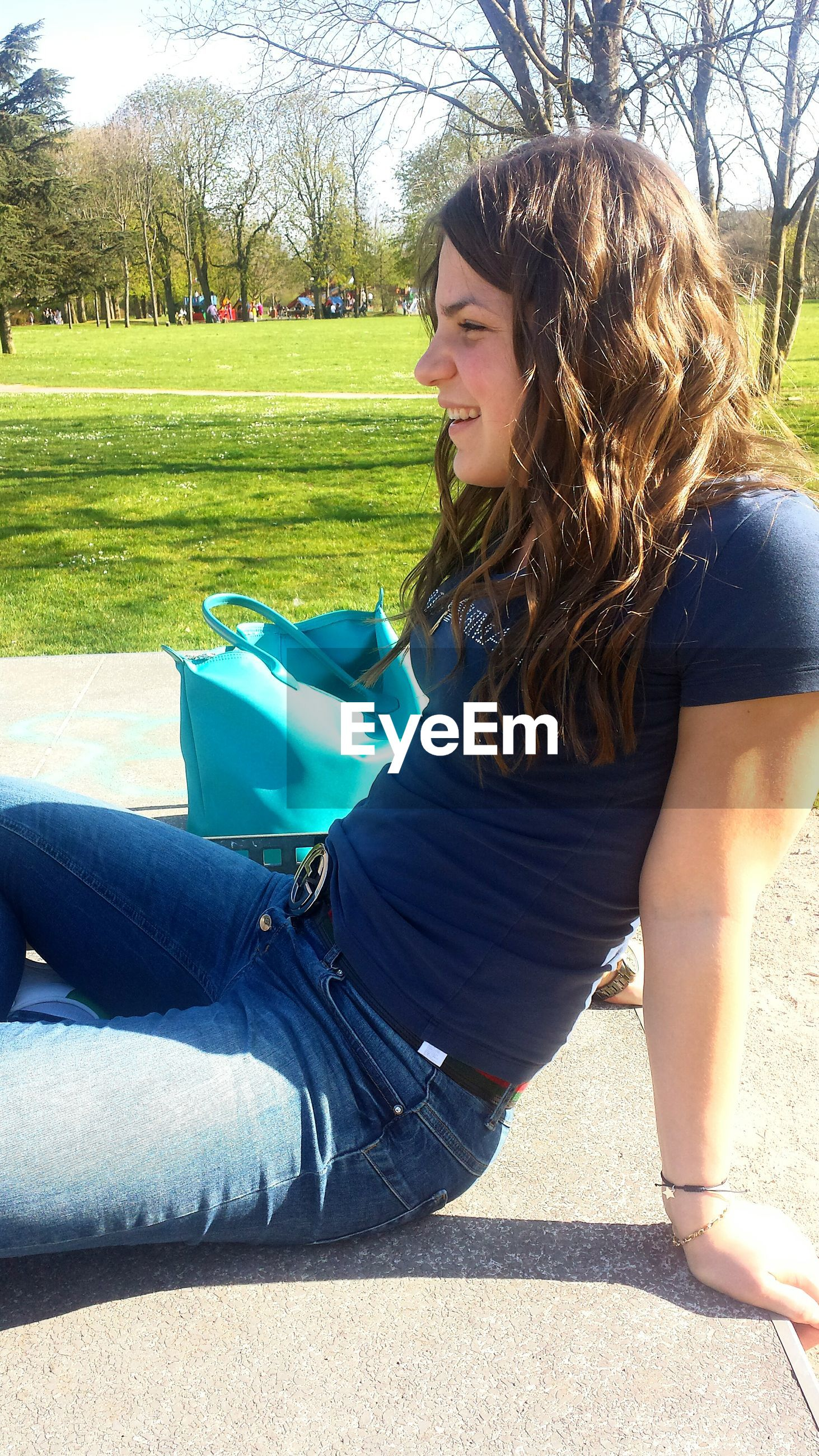leisure activity, lifestyles, sunlight, tree, person, casual clothing, young adult, park - man made space, childhood, shadow, relaxation, young women, sitting, grass, day, outdoors, sunglasses, side view