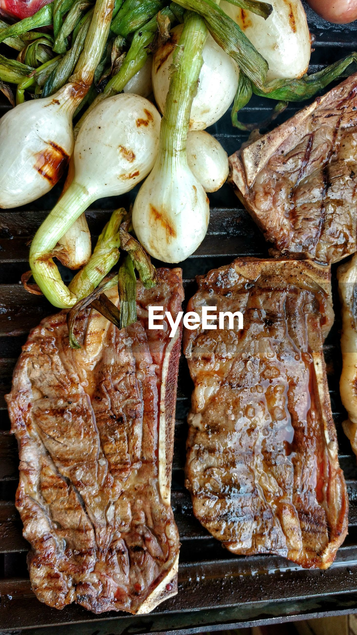Directly above shot of meat with vegetables on barbecue grill
