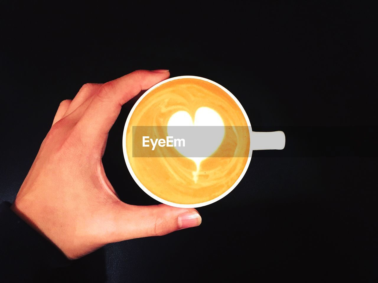 Cropped hand of woman holding cappuccino on black background
