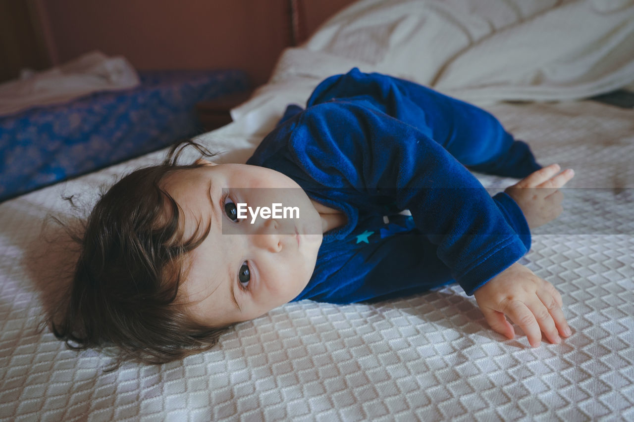 PORTRAIT OF BABY LYING ON BED AT HOME