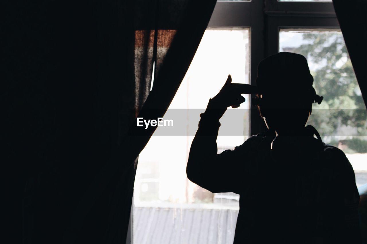 Silhouette Man Gesturing Gun Sign At Home