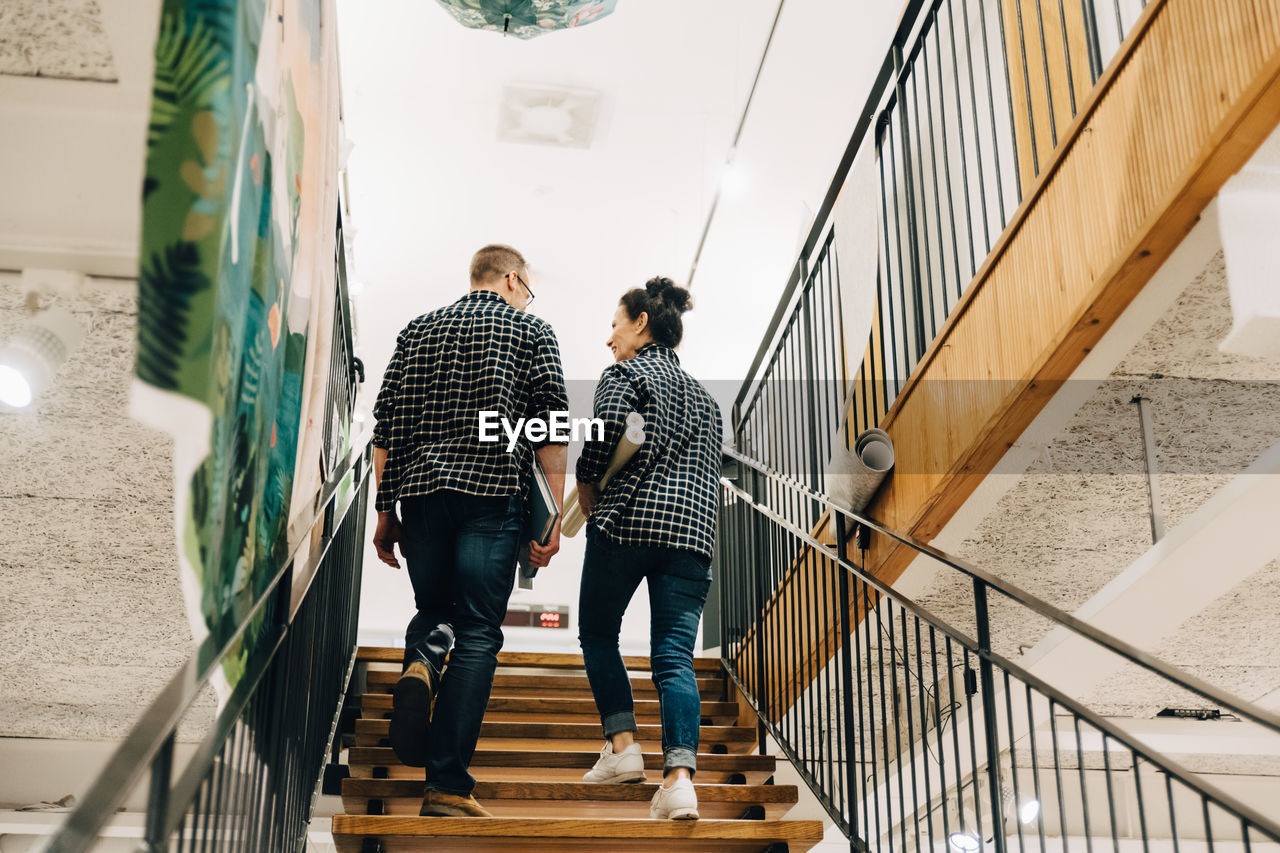 REAR VIEW OF FRIENDS WALKING ON STAIRCASE