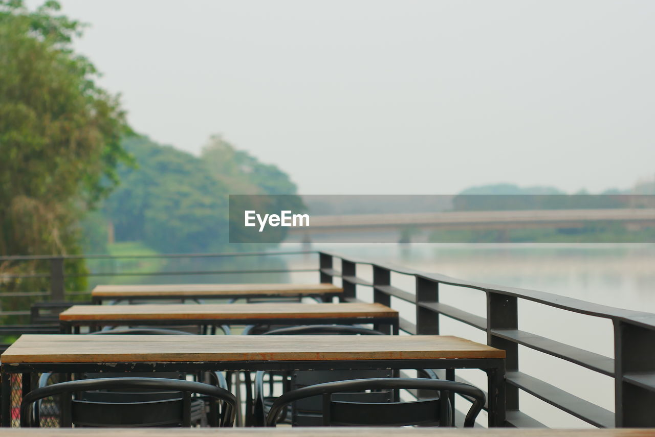 table, railing, seat, sky, no people, water, nature, chair, day, empty, tranquility, absence, focus on foreground, tree, wood - material, plant, outdoors, lake, beauty in nature, swimming pool