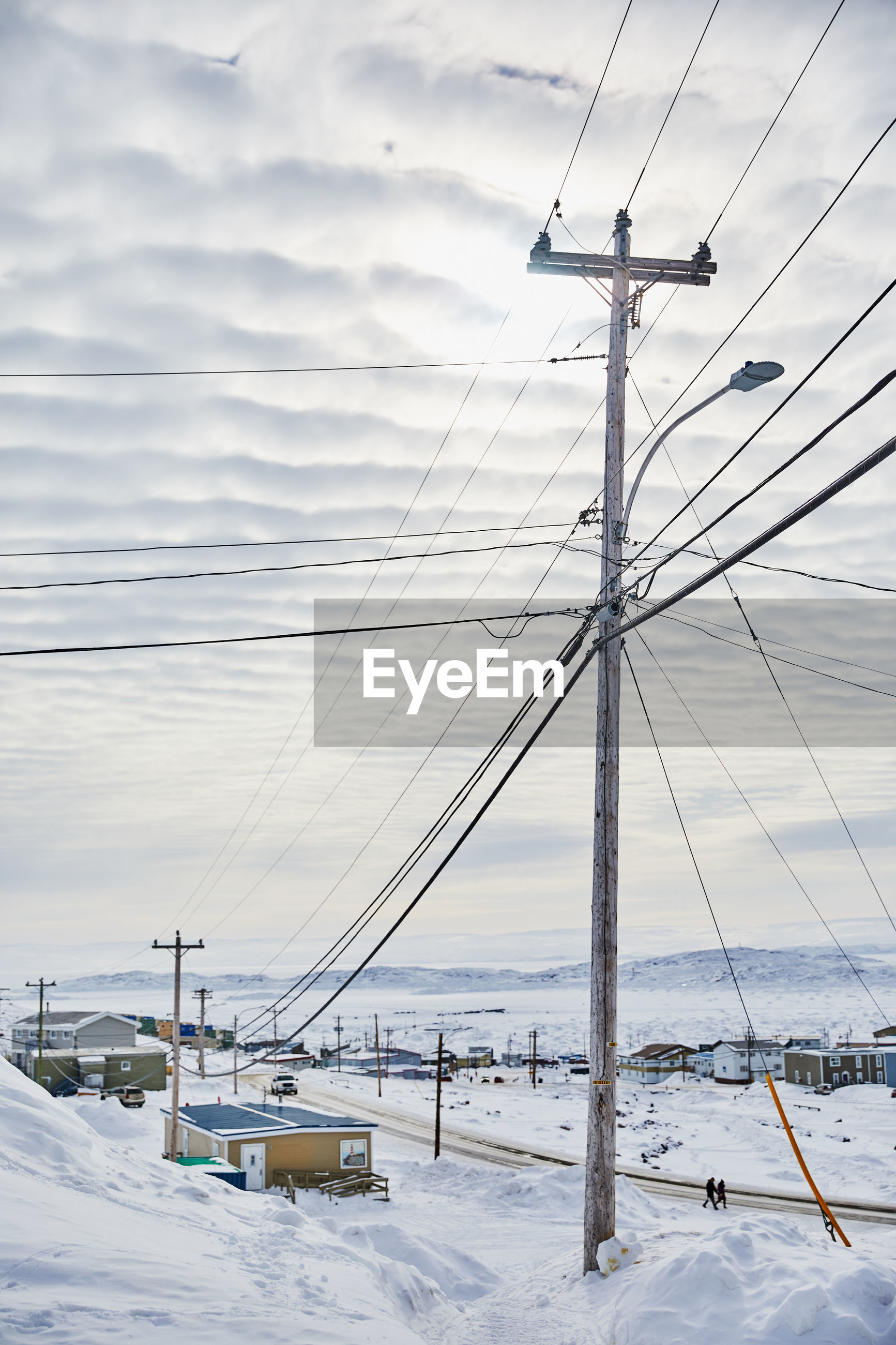 Power lines against sky during winter