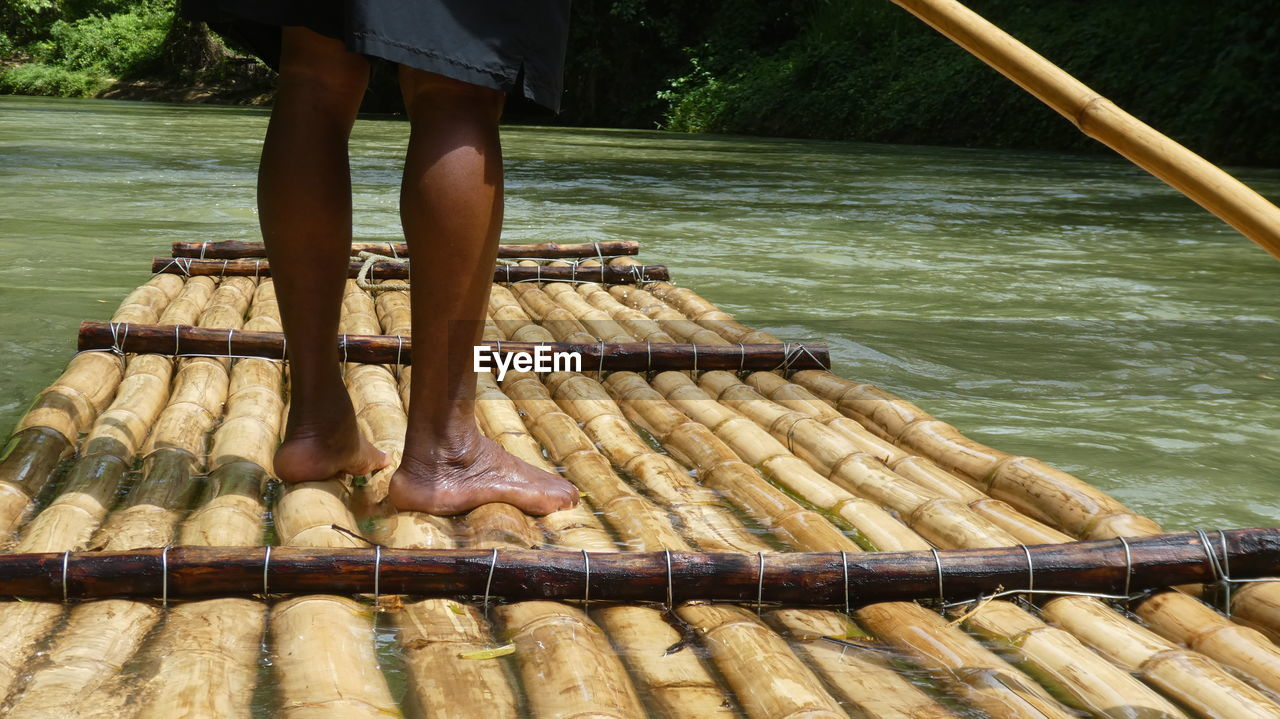 Low section of person standing on bamboo boat in lake