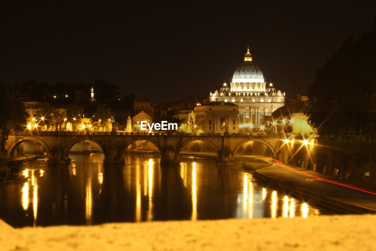 Illuminated St Peter Basilica By Bridge Over River At Night