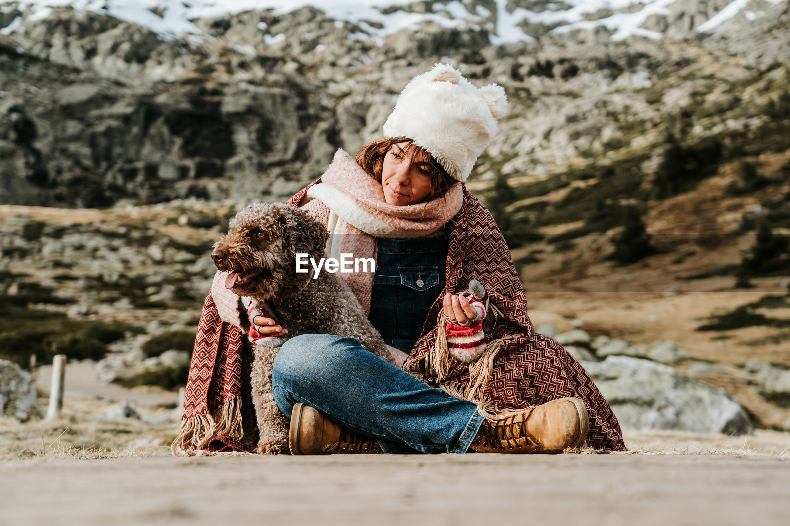 Woman wearing knit hat sitting in footpath with dog against field