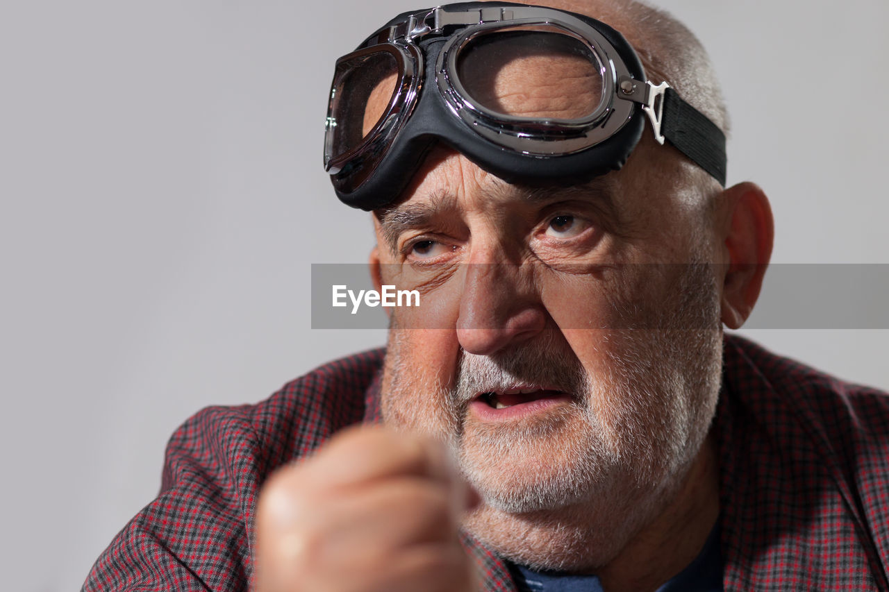 Close-Up Of Senior Man With Flying Goggle Looking Away Against White Background