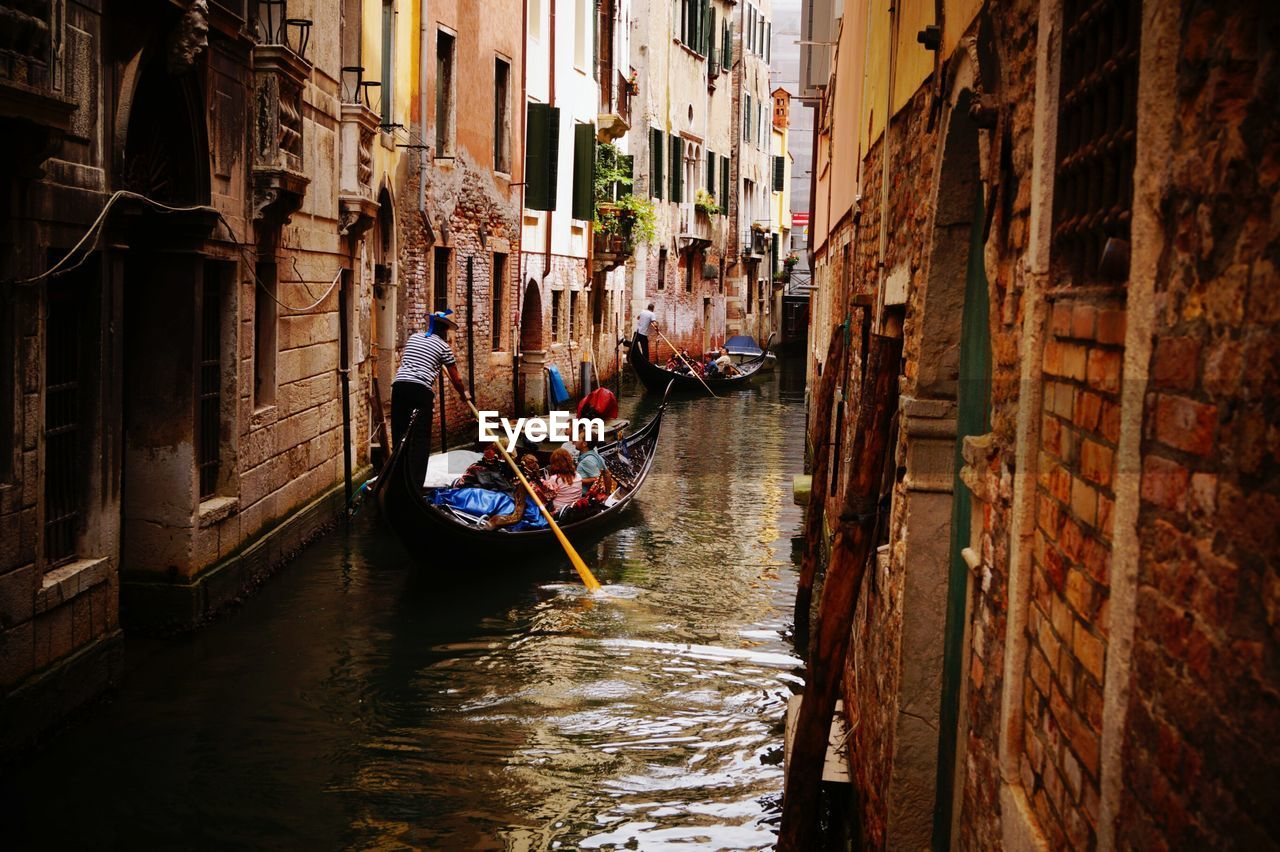 canal, gondola - traditional boat, gondolier, architecture, transportation, real people, building exterior, built structure, two people, nautical vessel, men, gondola, mode of transport, rowing, oar, day, outdoors, water, adult, people