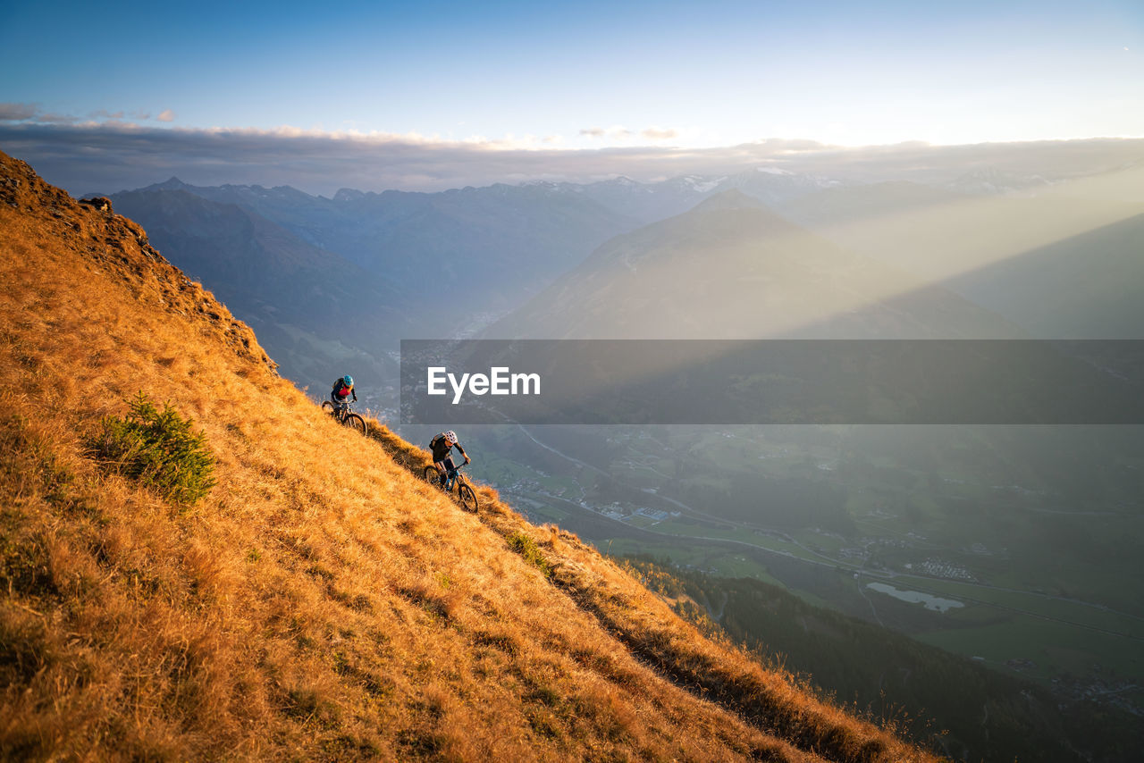 People riding bicycles on mountain against sky