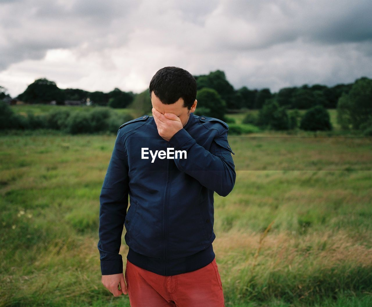 Man With Hands Covering Face Standing On Grassy Field Against Sky